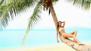 Relaxed woman resting on palm tree at the beach