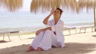Relaxed woman under shade umbrella at beach