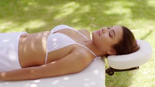 Relaxed young woman lying on her back on an outdoor spa bed in a white bikini top and white towel with her eyes closed in bliss.