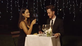 Romantic couple dining in an elegant restaurant raising their glasses of wine in a celebratory toast with happy smiles