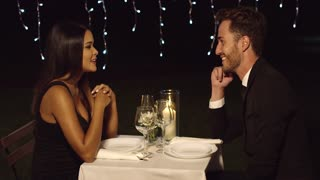 Romantic sexy couple enjoying an evening dinner at an upmarket restaurant sitting chatting and holding hands side view