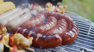 Sausages and vegetables cooking on grill