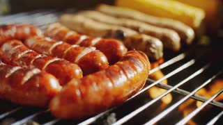 Sausages grilling over the flames