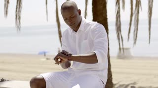 Seated black male model checking his watch