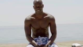 Seated muscular black man near beach and ocean
