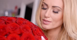 Seductive Blond Woman Behind Red Rose Bouquet