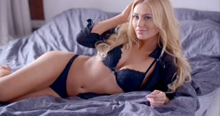 Seductive Blond Woman in Lingerie Lying on Bed