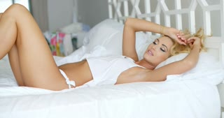 Seductive Young Woman Resting on White Bed