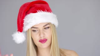 Sensual girl in Santa Claus hat posing isolated on gray background. Her beautiful lips are painted with red lipstick. She looking at camera.