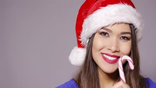 Sensuous young woman in a red Santa hat sucking on a colorful red and white striped candy cane with enjoyment as she celebrates the Christmas season.