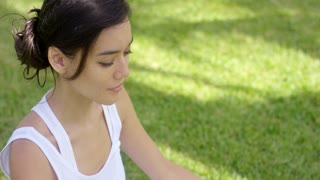 Serene young woman meditating on a green lawn with her eyes closed and smile of bliss