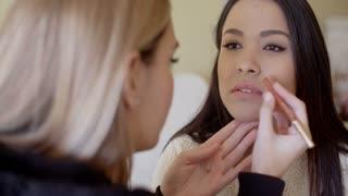 Serious woman getting lip liner makeup