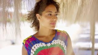 Serious woman under thatch beach umbrella
