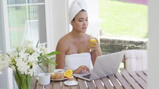 Serious young adult woman wrapped in towel having breakfast while seated in front of her laptop computer