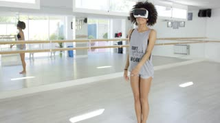 Sexy african american woman dancing with Virtual Reality glasses on her eyes. She practicing moves in modern dance studio.