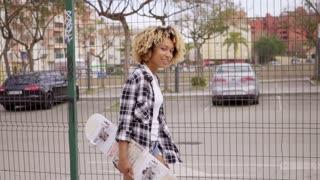 Sexy beautiful girl walking with skateboard