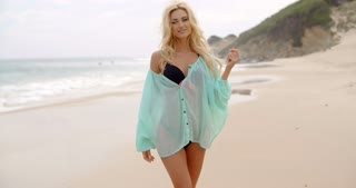 Sexy Blond Woman in Summer Outfit at the Beach