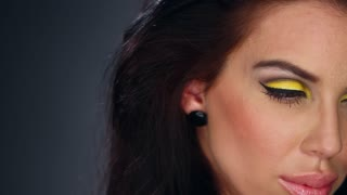 Sexy brunette in outstanding yellow makeup