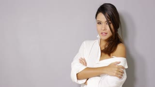 Sexy brunette latina woman posing in white male shirt with bare shoulder. She smiling to the camera. Isolated on gray background with copy space.