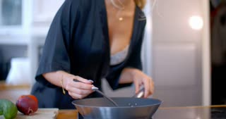 Sexy busty woman cooking in the kitchen