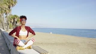 Sexy fashionable young woman at the seaside sitting on a beachfront wall in a trendy red outfit and sunglasses in the summer sun