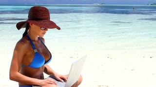 Sexy Girl in Bikini Working on Laptop Computer at the Exotic Beach