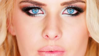 Sexy pensive blue-eyed blond woman with heavy modern creative eye makeup closeup of her face