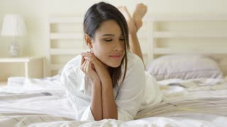 Sexy pretty barefoot young woman in fresh white sleepwear lying on her stomach on her bed giving the camera a sultry look