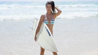 Sexy pretty young woman surfer carrying her surfboard along the beach standing smiling at the camera in front of a calm ocean and surf