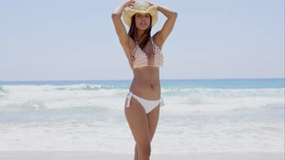 Sexy shapely young woman in a bikini and sunhat standing on a tropical beach looking to the side with a thoughtful expression with copy space