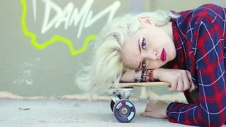 Sexy sultry young blond woman with a lip piercing lying relaxing on her skate board at the skate park looking at the camera with a serious expression.