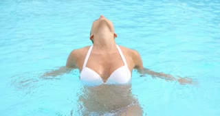 Sexy Woman in a Pool Water Holding her Neck