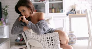 Sexy Woman in Gray Cardigan Sitting on a Chair
