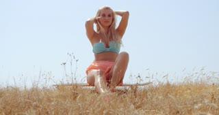 Sexy Woman Sitting o Skateboard at Grassy Beach