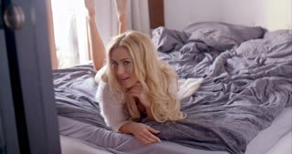 Sexy Young Blond Woman in Lingerie Lying on Bed