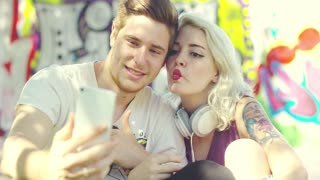 Sexy young blond woman pouting for a selfie with her boyfriend puckering up her mouth for a kiss as they pose in front of colorful graffiti.