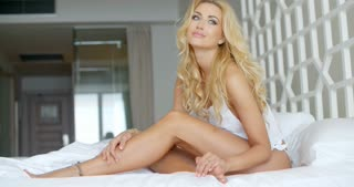 Sexy Young Blond Woman Sitting on White Bed