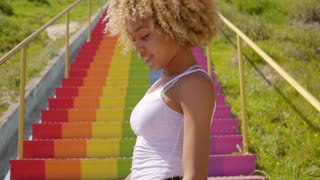 Sexy young woman dancing on rainbow colored steps
