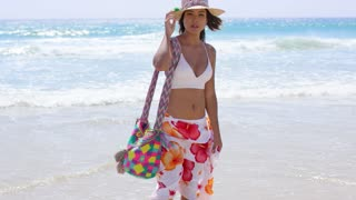 Sexy young woman posing on a tropical beach in a colorful sarong holding her straw sunhat in the breeze with a joyful friendly smile ocean background.