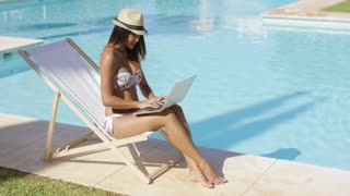 Sexy young woman relaxing at the swimming pool sitting in a deck chair in bikini and trendy hat working on a laptop