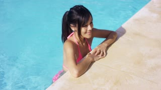 Sexy young woman standing in a swimming pool resting her hands on the tiled surround as she watches something off frame