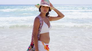 Sexy young woman strolling on a tropical beach in a bikini sunhat and sarong turning to give the camera a thoughtful look with the breeze blowing her hair.