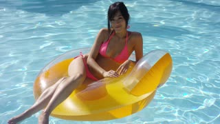 Sexy young woman sunbathing in a swimming pool relaxing on a colorful yellow tube in her pink bikini with a happy smile