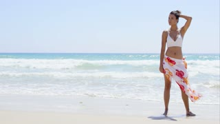 Sexy young woman walking through the shallow surf on a tropical beach in a sarong and bikini looking to the side with a thoughtful expression with copy space.