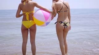 Shapely bodies of two girls with a beach ball
