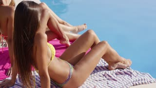 Shapely young woman in a bikini sitting at the edge of a swimming pool sunbathing with her friends
