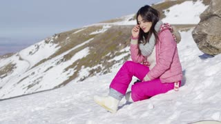 Side view of smiling young woman in pink snowsuit sat on snowy mountain summit looking over shoulder