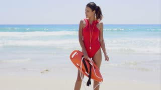 Side view on beautiful young woman with pony tail in red swimsuit with buoy on beach with waves from ocean