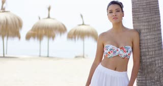 Single attractive young woman in floral pattern bikini and serious expression leaning against palm tree on beach with palapa umbrellas in background