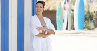 Single attractive young woman with joyful expression tied back hair and white robe over bathing suit standing near surf boards
